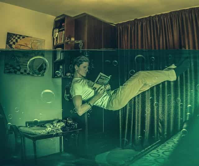 部屋の中で水に浮いて読書する男性