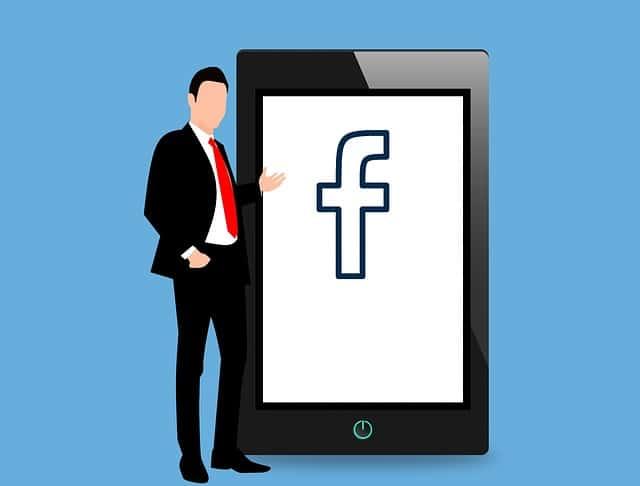 巨大スマホの中のFacebookのFのロゴとそのスマホの横に立つ男性