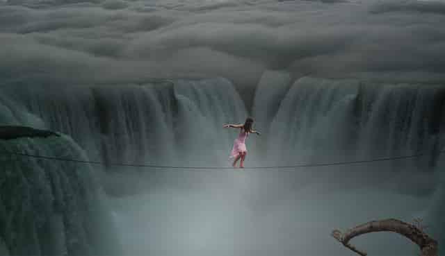 リスクのイメージで女性が巨大な滝を綱渡りしている様子
