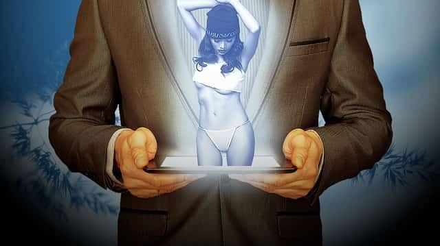 男性が持つタブレットの画面に女性のホログラフ